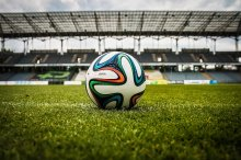 A football lying on the grass of a football pitch in a stadium